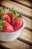 Strawberries in ceramic bowl. Strawberries in white ceramic bowl on wooden table Royalty Free Stock Image