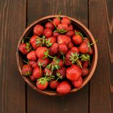 Strawberries in ceramic bowl on wooden background top view Stock Photography