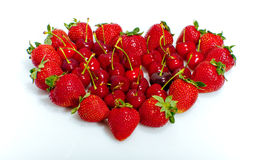 Strawberries and cherries. Straberries and cherries on a heart shape in white background Royalty Free Stock Image
