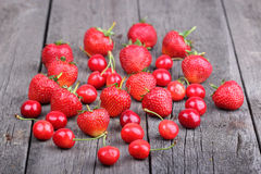 Strawberries and cherries on the old wood background Stock Images