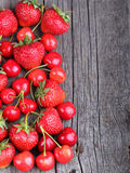 Strawberries and cherries on the old wood background Stock Photo