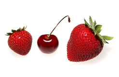 Strawberries and cherry. Two strawberries and a cherry on white background Royalty Free Stock Photography