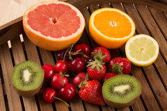 Strawberries, cherry, grapes, kiwi, orange and grapefruit on a plate. Fruit platter. Royalty Free Stock Images