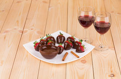 Strawberries in chocolate with cinnamon on wood. Royalty Free Stock Photography