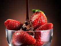 Strawberries and chocolate. Chocolate cream poured over a bed of strawberries Stock Image