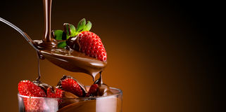 Strawberries and chocolate. Chocolate cream poured over a bed of strawberries Royalty Free Stock Photos