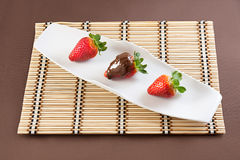 Strawberries with chocolate. On table mat for Valentine's day or other love related situation Royalty Free Stock Images