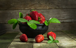 Strawberries in a clay bowl. On a wooden background royalty free stock photography