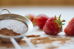 Strawberries. With cocoa lying on a white table Royalty Free Stock Images