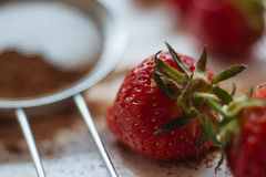 Strawberries. With cocoa lying on a white table Royalty Free Stock Photos