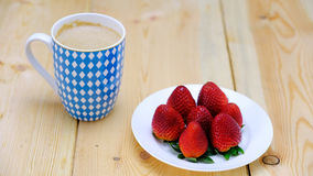 Strawberries and coffee. Strwberries on white porcelain plate and coffee in blue and white cup on planks of pine wood stock images