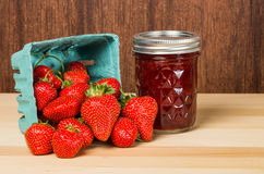 Strawberries in container with jam or jelly Royalty Free Stock Photo