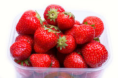 Strawberries in a container for sale. Juicy, ripe strawberries in a plastic container on a white background. Partly in the frame, close-up view from above Royalty Free Stock Photography