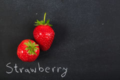 Strawberries. A couple of  strawberries on dark black chalkboard. Concept Royalty Free Stock Photos
