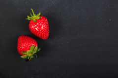 Strawberries. A couple of strawberries on a dark black chalkboard with copy space Stock Photo