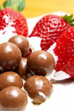 Strawberries and cream. Three strawberries with chocolate balls lying in cream on white saucer stock image