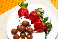 Strawberries and cream. Three strawberries with chocolate balls lying in cream on white saucer stock photography