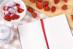 Strawberries cream background, recipe book, cookbook, copy space. Strawberries and cream with blank recipe book on a chopping board and check tablecloth Stock Photos