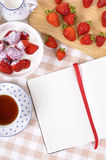 Strawberries cream background, table, bowl, recipe book, copy space Stock Photography