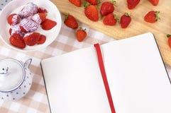 Strawberries cream bowl, recipe book, copy space Stock Images