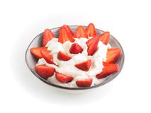 Strawberries with cream in a ceramic bowl with white background.  royalty free stock photography