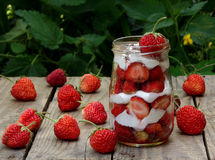Strawberries and cream in a jar. On a wooden background stock image