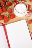 Strawberries cream jug, recipe book, cookbook, copy space. Strawberries and jug of cream with blank recipe book on a chopping board and red check tablecloth Royalty Free Stock Images