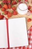 Strawberries cream jug summer background, recipe notebook, copy space Stock Image