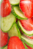 Strawberries and cucumbers swim in the sparkling water. Stock Images