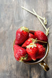 Strawberries in cup over wooden table Stock Photography