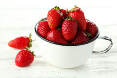 Strawberries in cup on a white wooden background Royalty Free Stock Photo