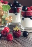 Strawberries,currants and raspberries with cottage cheese and sour cream on the dark wooden table. Selective focus.  Stock Images