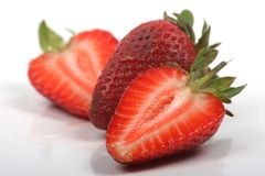 Strawberries cut in half. Fresh strawberries cut in half on a white background stock image