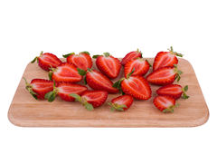 Strawberries cut into halves. Fresh ripened strawberries cut into halves arranged on kitchen board stock photo