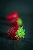 Strawberries on dark background with water drops royalty free stock images