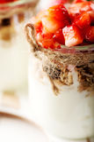 Strawberries desert with cream and cereals. Served on glass cups over white table Royalty Free Stock Images