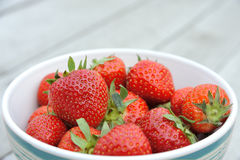 Strawberries in a dish. Strawberries ready to be eaten, dispayed in a dish on a wooden table in a shallow depth of field Royalty Free Stock Photography