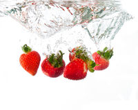 Strawberries dropped into water splash Royalty Free Stock Images