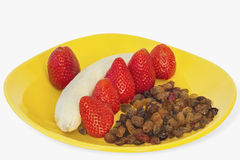 Strawberries Dry Grapes And Banana On Yellow Plate. Photograph of six Strawberries with bunch of dry Grapes and peeled off Banana on yellow plate Royalty Free Stock Image