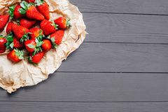 Strawberries in a on eco craft paper on a wooden eco background with greens. stock photo