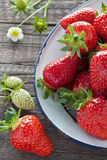 Strawberries in enamel bowl. Freshly picked strawberries in an enamel bowl on wooden background Royalty Free Stock Images