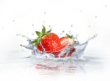 Strawberries falling into clear water, forming a crown splash. vector illustration