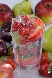 Strawberries falling in glass of water. Other fruit around Royalty Free Stock Photos