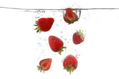 Strawberries Falling Into Splashing Clear Water Royalty Free Stock Photo