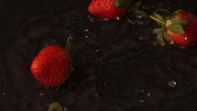 Strawberries falling on wet black surface stock video