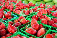Strawberries at Farmer's Market. A collection of fresh strawberries are gathered in baskets on a sale table at a farmer's market Royalty Free Stock Photo