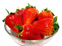 Strawberries in February. Red juicy strawberries in glass dish on white Stock Images
