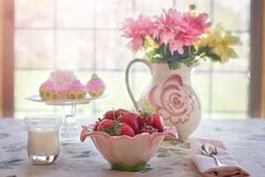 Strawberries and flowers on table Royalty Free Stock Photos