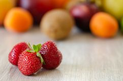 Fresh colorful fruits. Strawberries in the foreground, Healthy nutrition, diet concept. Strawberries in the foreground, colorful fruit in the background royalty free stock image
