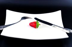 Strawberries, fork and knife on a plate Stock Photography
